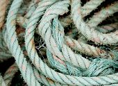 Photo of an old worn rope rolled in green