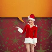 Pretty santa girl presenting with hand against red vignette