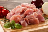 Raw turkey meat on cutting board on wooden background