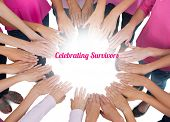 Hands joined in circle wearing pink for breast cancer on white background