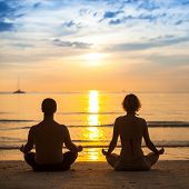 Young couple practicing yoga on sea beach during amazing sunset.