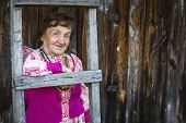 Old woman in Slavic folk clothes on his farm in the village.