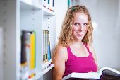 Pretty, young college student female college student in a library (shallow DOF; color toned image)