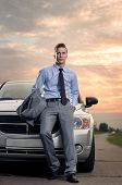 Handsome young man leaning on his car. Attractive gorgeous guy standing, outdoors - outside