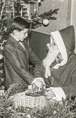 CRANS, SWITZERLAND, DECEMBER 27, 1956: Vintage photo of Santa Klaus giving gift to little boy