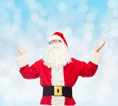 christmas, holidays and people concept - man in costume of santa claus with raised hands over blue lights background