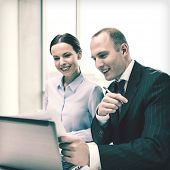 business, technology and office concept - businessman and businesswoman with laptop computer and papers having discussion in office