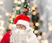 christmas, holidays and people concept - close up of santa claus in glasses winking over tree lights background