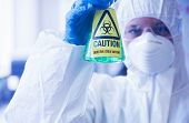 Scientist in protective suit holding beaker with caution sticker