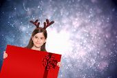 Festive little girl showing card against red christmas ribbon
