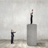 Businesswoman standing on top and looking down at colleague