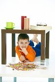 Happy little kid eating sweets under table at home. Lying on belly, happy, smiling, isolated on white