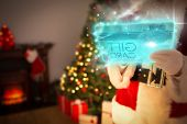 Composite image of santa using futuristic touchscreen at home before christmas
