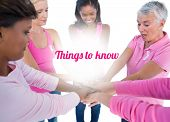 Women wearing pink and ribbons for breast cancer putting hands together on white background