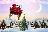 Santa flying his sleigh against cute christmas village with tree