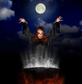 stock photo of witches cauldron  - Young witch with cauldron on night sky background - JPG