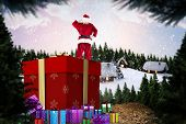 Santa standing on giant present against cute village in the snow