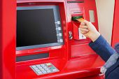 Woman inserting credit card into ATM