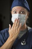 Shocked Looking Female Doctor or Nurse with Hand in Front of Mouth.