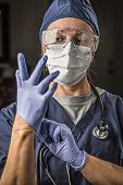Concerned Female Doctor or Nurse Putting on Protective Facial Wear and Surgical Gloves.