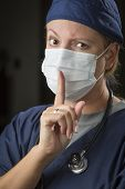Secretive Female Doctor or Nurse with Finger in Front of Mouth.