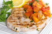 Grilled marlin steak served with an onion, garlic and tomato salsa, sliced lemon and parsley