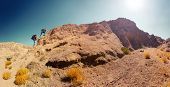 Panorama of two hikers crossing rocky terrain in the desert at sunny day
