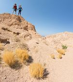 Two hikers standing on top of the mountain in the desert at sunny day