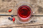 Cup Of Red Tea With Wild Berries On Wood Background