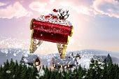 Santa flying his sleigh against digitally generated snowy land scape