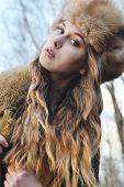 picture of early 20s  - portrait photo of blond hair wind girl looking to camera wearing fur hat in early spring - JPG