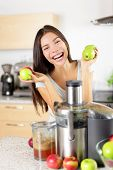 Apple juice - Woman making apple juice on juicer machine at home in kitchen. Juicing and healthy eating happy woman making green vegetable and fruit juice. Mixed race Asian Caucasian model.