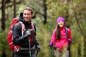 Hiking man and woman on hike in forest trekking. Couple on adventure trek in beautiful forest nature. Multicultural Asian woman and Caucasian man living healthy active lifestyle in woods.