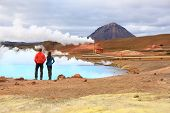 Iceland travel people by geothermal energy power plant and hot spring in Namafjall in Lake Myvatn area. Couple on travel in Icelandic nature landscape, Route 1 Ring Road.