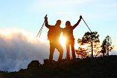 Success, achievement and accomplishment concept with hiking people cheering and celebrating of joy with arms raised outstretched up on trekking hike outside. Hikers having fun at sunset.