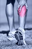 Muscle injury - Man running clutching calf muscle after spraining it while out jogging on the beach. Male athlete sport injury.