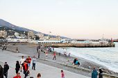 Tourists On Pebble Beach Of Yalta City In Evening