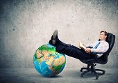 Young handsome businessman sitting in chair with book in hands. Elements of this image are furnished by NASA
