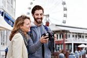 young couple taking pictures on holiday at tourist attraction