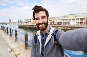 Backpacker man taking selfie on holiday having fun and smiling