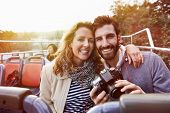 portrait of couple enjoying holiday vacation sightseeing bus open top tour