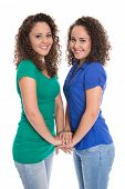 Isolated smiling young girls: real twin siblings holding hands together.