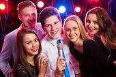 Young people singing into microphone at party