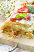 traditional apple strudel with strawberries and powdered sugar
