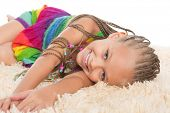 Cute girl with dreadlocks lays on the mat. Girl six years.