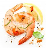 Cooked shrimp, spices and lemon slice on white background.