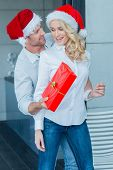 Husband surprising his wife with a Christmas gift reaching round from behind her with a smile with a red gift wrapped box  both in Santa Hats