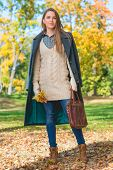 Full Length Pretty Blond Young Woman Holding Leather Bag and Flower in Autumn Fashion Outfit. Captured Outdoor.