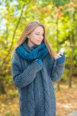 Young woman in a warm knitted blue ensemble using a mobile phone outdoors in autumn as she stands amongst colorful fall trees