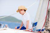 Cute teenage boy enjoying sailing on a luxury catamaran or yacht